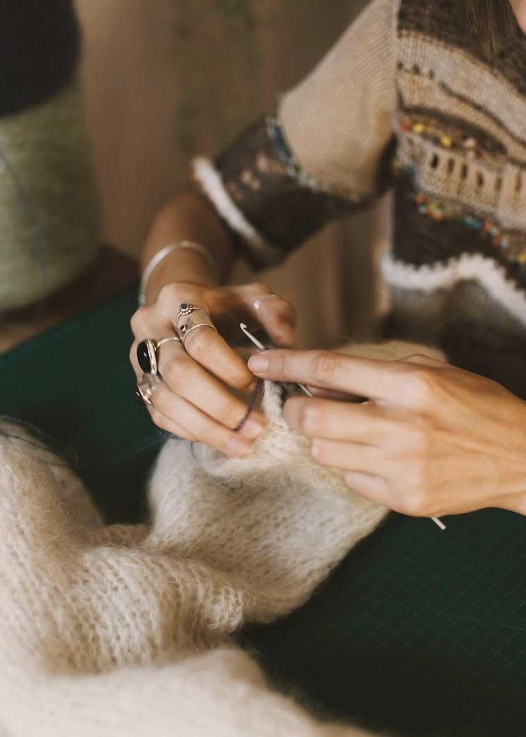 Leandi hand knitting a piece.
