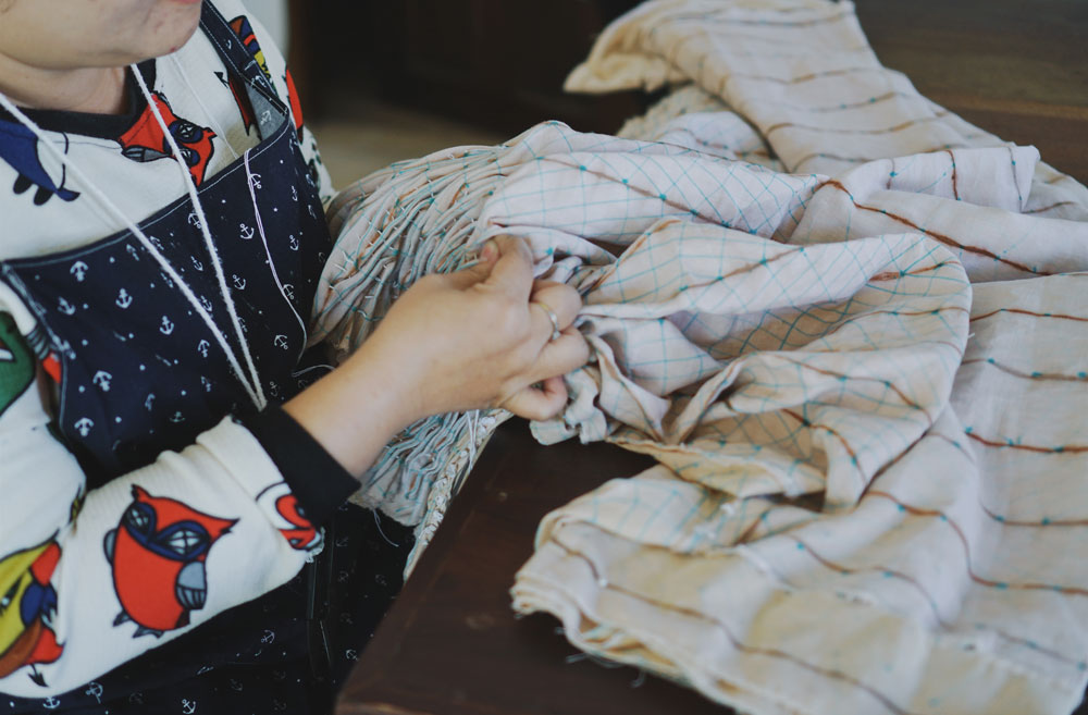 One of their team stitching a piece of fabric.
