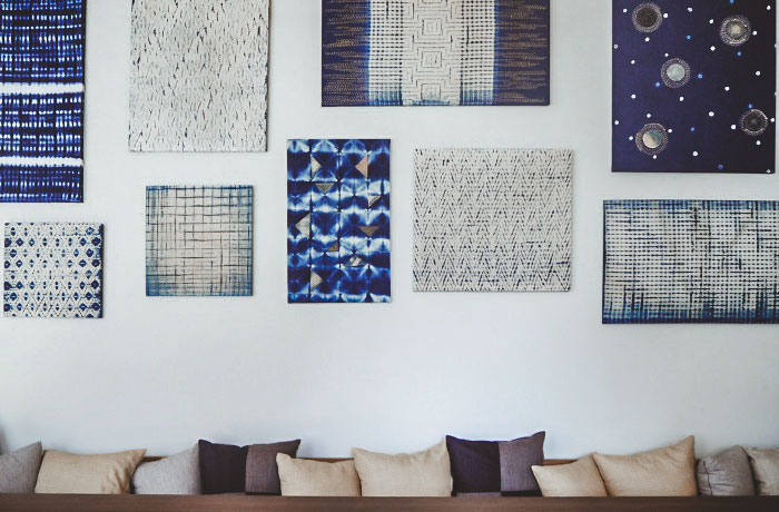 A wall decorated with hand-dyed textiles.